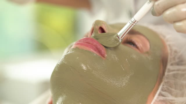a close up view of woman's face with green mask. a hand with a brush applies more mask under the nose above the upper lip - viziarsi video stock e b–roll