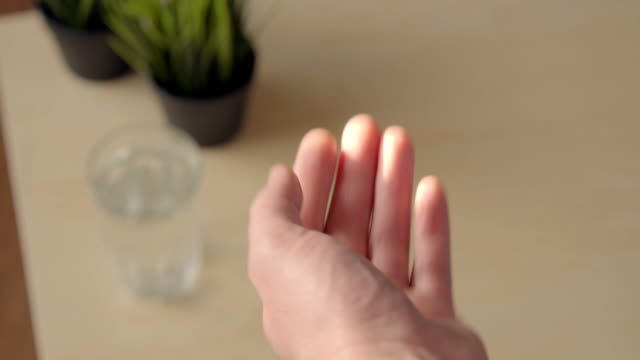 Close up view of young woman holding ginseng vitamins and minerals pills in hand and taking glass of water. High angle view. video