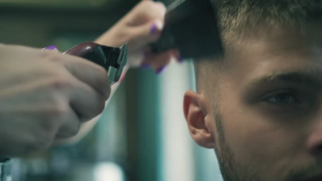 Close up view on male haircut with electric razor. Professional barber is styling man's hair with trimmer. Man hairdressing with electric shaver video