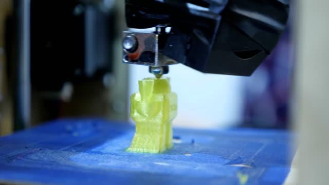 nahaufnahme, eine dreidimensionale plastikfigur auf einem dreidimensionalen drucker drucken - bio lebensmittel stock-videos und b-roll-filmmaterial