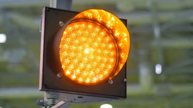 Close up view: signal LED orange traffic light blinking at transport exhibition