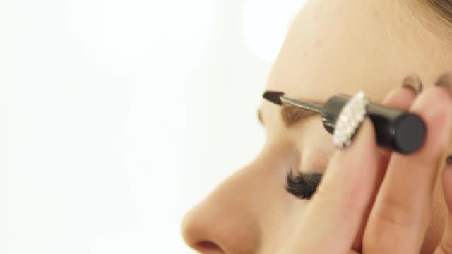 Visagist Kämmen Augenbraue mit Kosmetik Pinsel nach der Färbung im Make-up Studio hautnah. Professionelle Make-up Augenbrauen auf Lektion in Schönheitsschule – Video