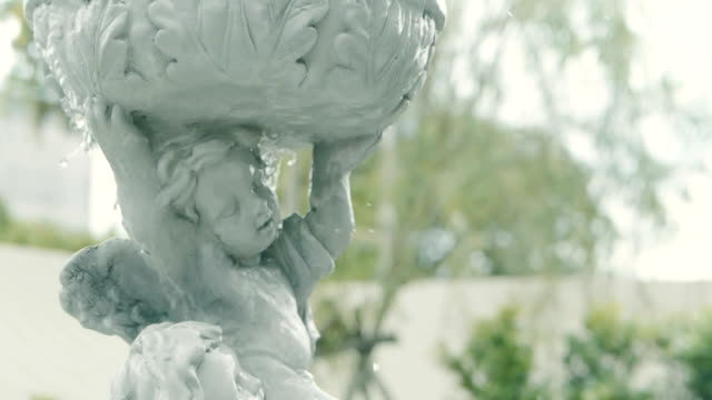 close up water flowing over  cupid fountain , English home garden style, slow motion