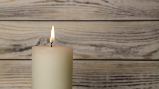 Close up white candle trembling flame over wood Close up one white candle trembling flame over background of white and brown wooden planks wall, off-center, fired up with lighter, burning and blown out, low angle side view candle stock videos & royalty-free footage