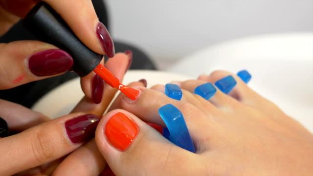 zbliżenie z technikiem paznokci stosując czerwony lakier do paznokci na paznokcie u łóżek klienta - pedicure filmów i materiałów b-roll