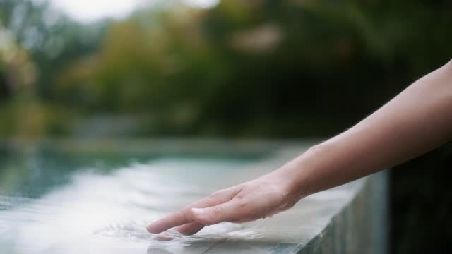 Close up, woman hand glides on water at edge of pool, slow motion