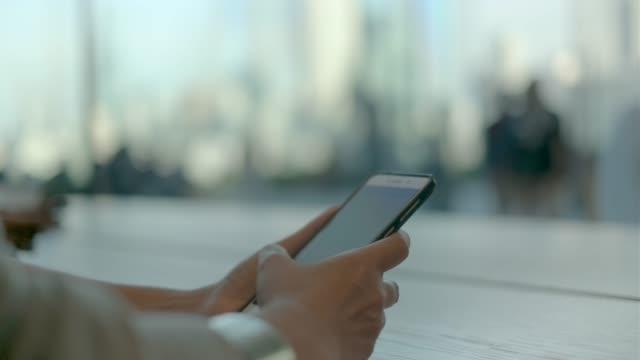 關閉婦女手使用手機在咖啡館桌子附近的視窗與人群在外面。 - 手提資訊設備 個影片檔及 b 捲影像