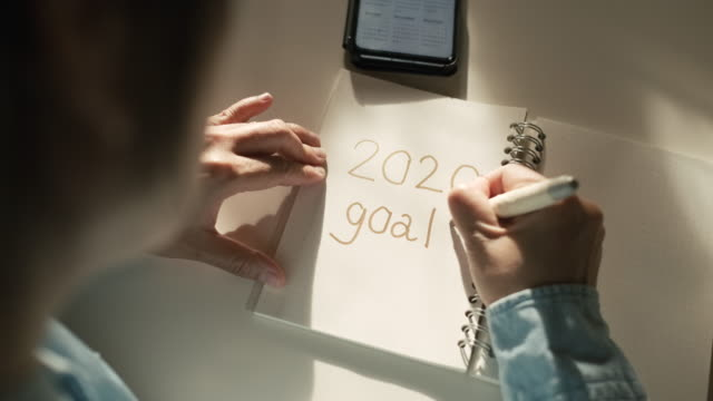 close up woman hand writing 2020 new year goals on notebook on desk with morning sunlight from window - to do list video stock e b–roll