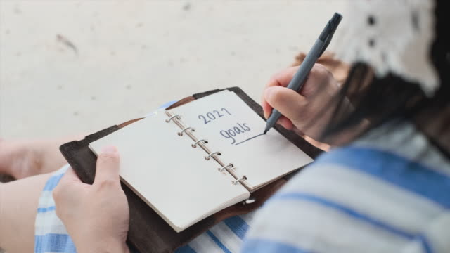 close up woman hand writing 2021 goals sitting at beach on summer vacation time