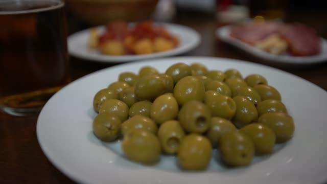 4k, close up donna mani tenendo un'oliva verde nel bar spagnolo. tapa tipica - antipasto video stock e b–roll