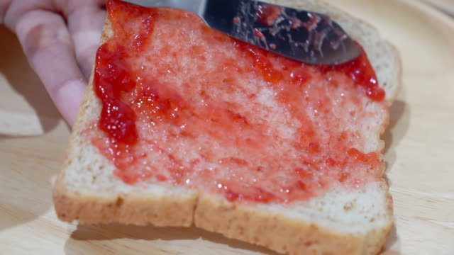 Close up, Woman holding knife spreading Jam strawberry on bread. Close up, Woman holding knife spreading Jam strawberry on bread. jello stock videos & royalty-free footage