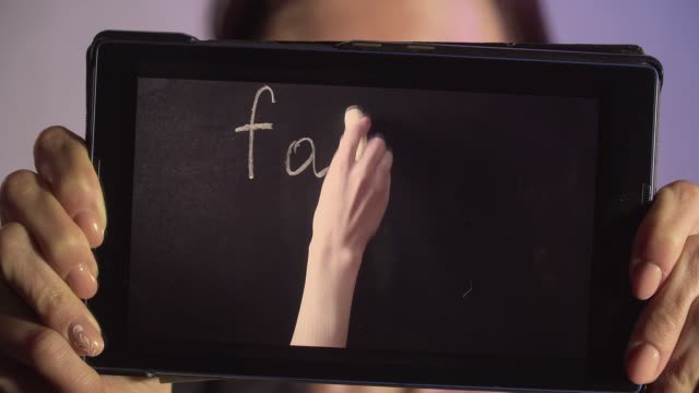 close up woman holding tablet pc with online teaching. hand writes on board words father and mother - {{relatedsearchurl(carousel.phrase)}} video stock e b–roll