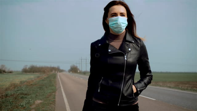 close up woman in protective face mask and black jacket walking across road for stopping car with suitcase on wheels and car passing by - donna valigia solitudine video stock e b–roll