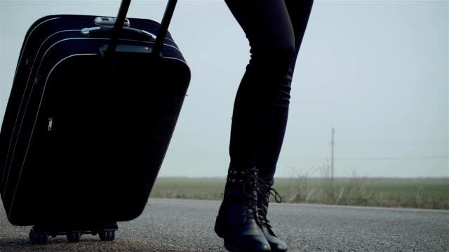 close up woman legs walks on asphalt road and traveling world with travel suitcase - donna valigia solitudine video stock e b–roll