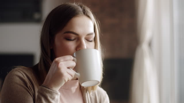 Close up, woman sitting in living room and drinking coffee Close up, young woman sitting in living room and drinking coffee mug stock videos & royalty-free footage