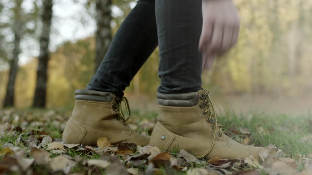 Close up, woman tying shoelaces on autumnal leaves