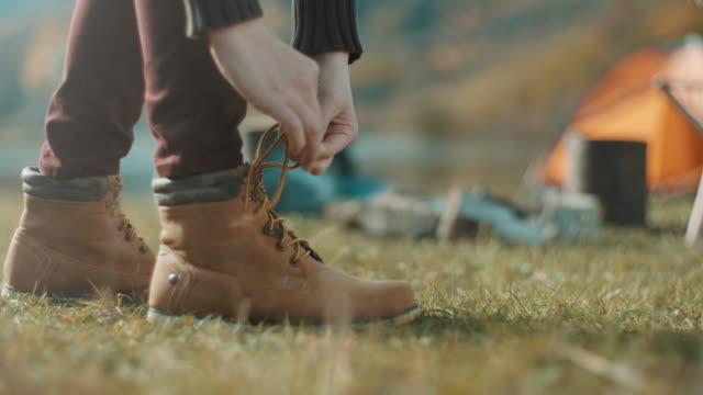 primo stato, donna che lega i lacci delle scarpe - annodare video stock e b–roll