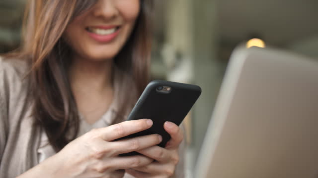 Close up Woman using smart phone with Laptop