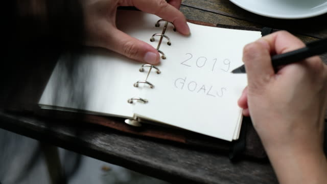 Close up woman writing 2019 goals on notebook plan for new year and drink coffee on wood table