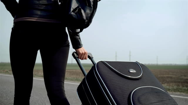 close up woman's hand holding suitcase and carrying it behind her alone - donna valigia solitudine video stock e b–roll