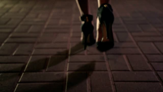 Close up women's legs walking away at night Close up elegant woman's legs on high heel shoes walking away on city street at night. Background night city lights human foot stock videos & royalty-free footage