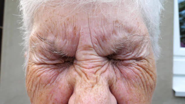 Close up wrinkled face of old grandmother looking into camera with a sad sight. Portrait of mature woman strongly screwing up her gray eyes. Sorrow facial expression of senior lady. Slow motion
