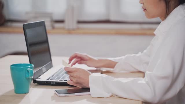 自宅でオンラインショッピングのためにクレジットカードとラップトップを使用して若いアジアの女性をクローズアップ - クレジット決済点の映像素材/bロール