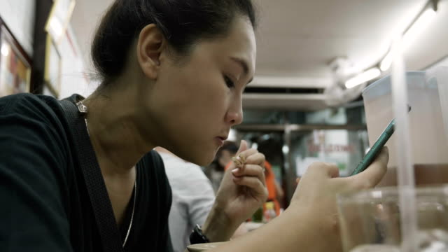 Close up Young Asian woman using mobile phone touchscreen ans eating. Close up Young Asian woman using mobile phone touchscreen ans eating. Thailand street food. scandal abc stock videos & royalty-free footage