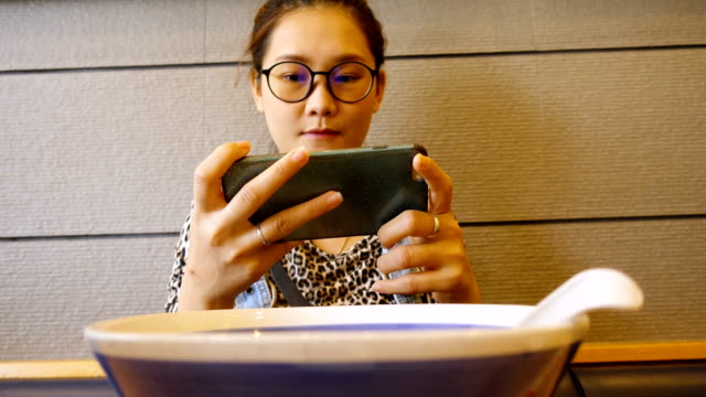 Close up Young Asian woman using mobile phone touchscreen eating Japanese noodle. Close up Young Asian woman using mobile phone touchscreen eating Japanese noodle. scandal abc stock videos & royalty-free footage