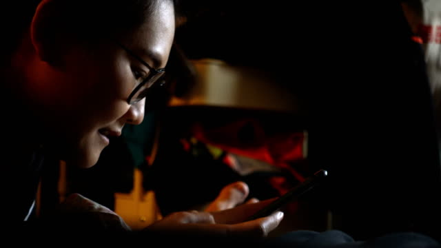 Close up Young Asian woman using mobile phone touchscreen on the bed. Close up Young Asian woman using mobile phone touchscreen on the bed. scandal abc stock videos & royalty-free footage