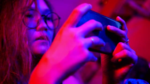 junge asiatin mit handy touchscreen rollenspiel in den raum mit rosa und blauen licht hautnah. - computerspieler stock-videos und b-roll-filmmaterial