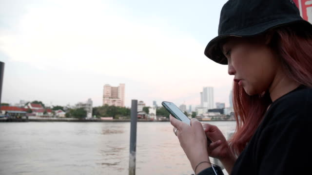 Close up Young Asian woman using mobile phone touchscreen. Slow motion : Close up Young Asian woman using mobile phone touchscreen in front of Chao Phraya River wait for Taxi boat , sunset. Bangkok. scandal abc stock videos & royalty-free footage