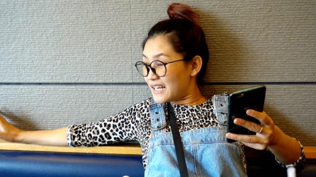 stockvideo's en b-roll-footage met jonge aziatische vrouw met behulp van de mobiele telefoon touchscreen close-up. - s