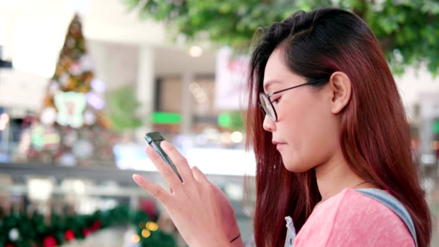 Close up Young Asian woman using mobile phone touchscreen with Christmas tree background.