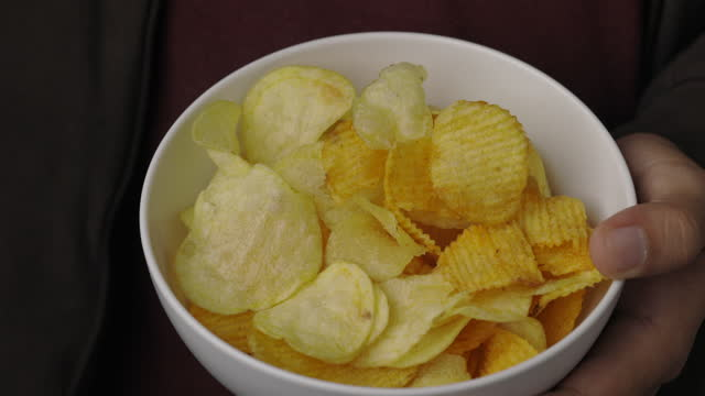 Close up young man eating crispy potato chips salty snacks in bowl. Fast food or junk food snacks unhealthy concept. Close up young man eating crispy potato chips salty snacks in bowl. Fast food or junk food snacks unhealthy concept. potato chip stock videos & royalty-free footage