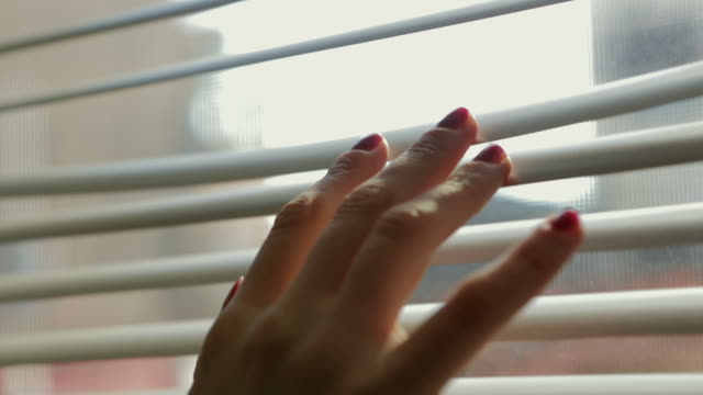 Close up Young woman female hand touching blinds Window Person video