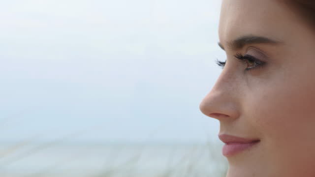 close up young woman looking at out to sea. - distrarre lo sguardo video stock e b–roll