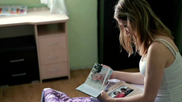 close up young woman looking at photobook in bedroom - foto video stock e b–roll