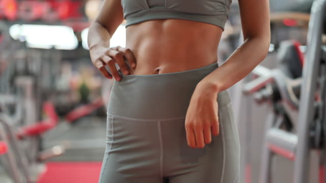 close up young woman with slim toned young body . an example of sports exercise at gym. fitness and healthy lifestyle concept. slow motion - tułów filmów i materiałów b-roll