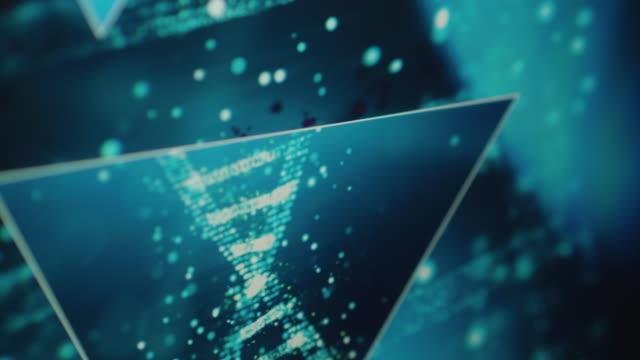 vídeos de stock e filmes b-roll de close ups of a futuristic dna research interface on a computer monitor - hélice formas geométricas