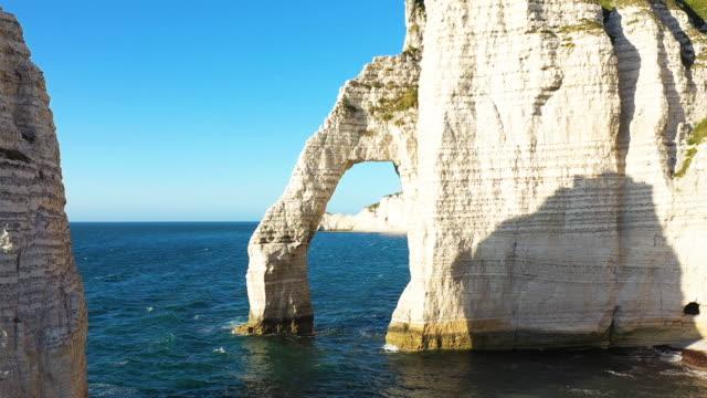 Close view of the cliffs of Etretat on a sunny cloudless day Cette photo a été prise en France, au nord de la Normandie, à Etretat et avec un drone. Il s'agit d'un passage sous la porte principale du lieu. cliffs stock videos & royalty-free footage