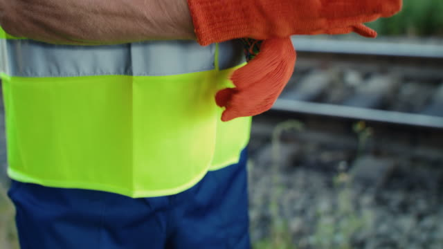 Close view of unrecognizable engineer dressing work gloves at railway video