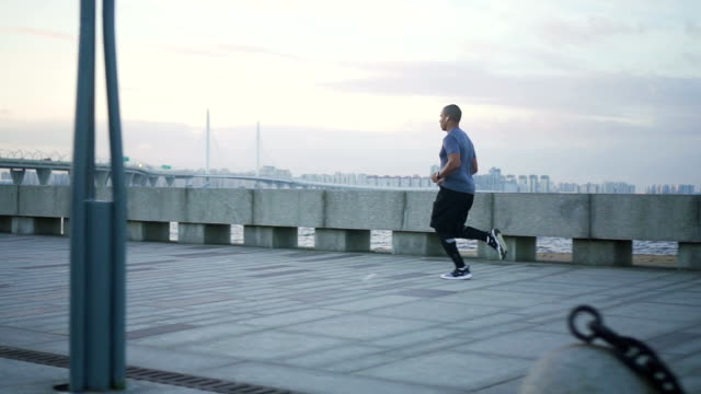 A close view of young black african american attractive fit and healthy man running on the sidewalk in the summer in slow motion