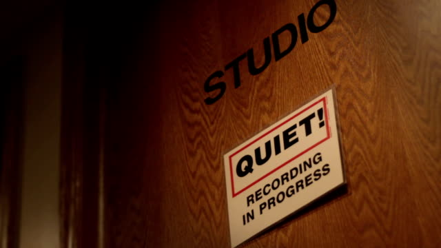 A closed door to a recording studio with a please be quiet sign - vídeo