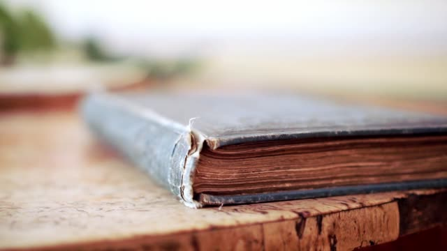 Closed old book on the old table Macro with cover of old book on the table textbook stock videos & royalty-free footage