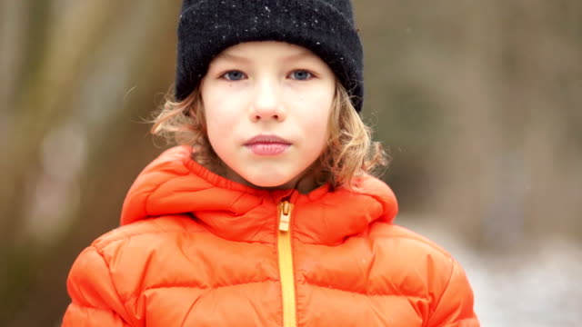 Closed portrait of a European boy in a winter hat. He's serious, and then he starts screaming video