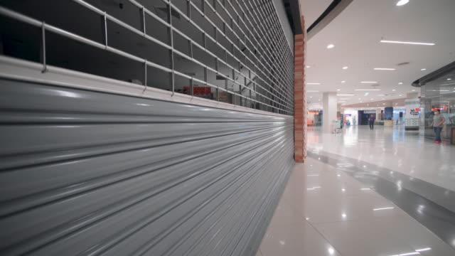 geschlossener laden im einkaufszentrum während der covid-19 pandemie. geschäfts- und personenkonzept - geschlossen allgemeine beschaffenheit stock-videos und b-roll-filmmaterial