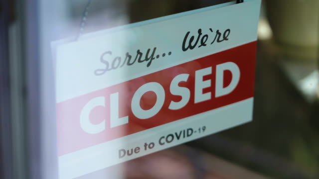 Closed sign hang on the glass in pandemic time in 4K Slow motion 60fps video