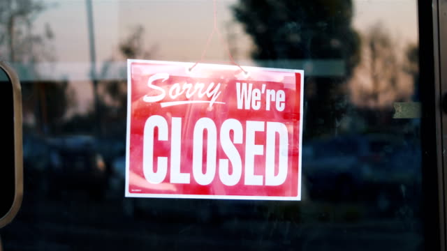 closed sign hanging on the door of a shop in 4k slow motion - bankruptcy stock videos & royalty-free footage