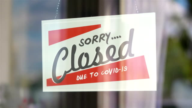 Closed sign hanging on the glass during pandemic time in 4K Slow motion 60fps video